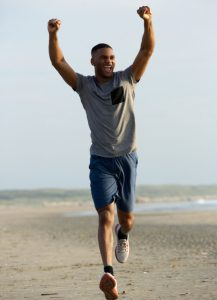 Young Man Running on Beach with Hands Raised